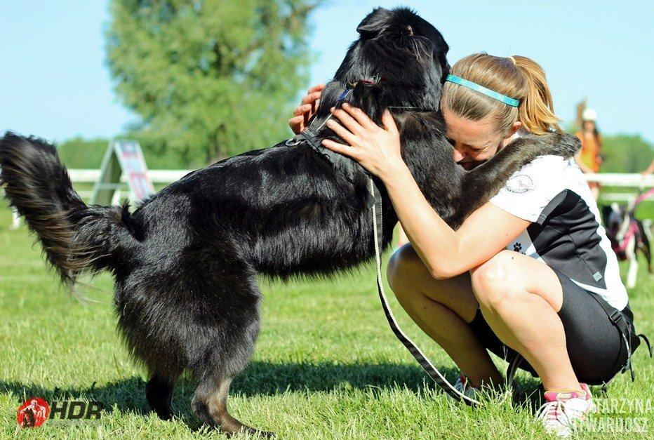 Fekete kutya és gazdája ölelkeznek