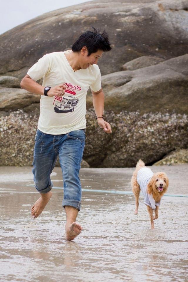 Strandon futó kutya gazdájával